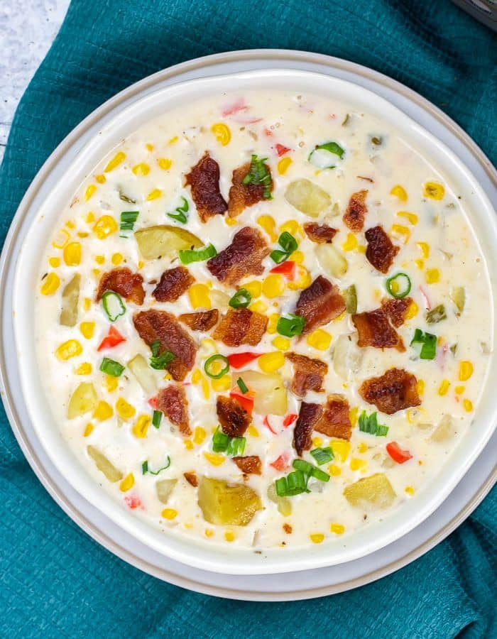 Overhead view of a white bowl of corn chowder topped with bacon and green onions sitting on a blue napkin.