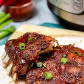 2 racks pork ribs on paper with partial view of Instant Pot and bowl of bbq sauce with red brush in the background.