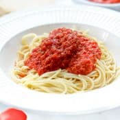 White bowl of spaghetti topped with marinara sauce with Roma tomato and garlic in the foreground and a small bowl of marinara sauce and bread in the background.