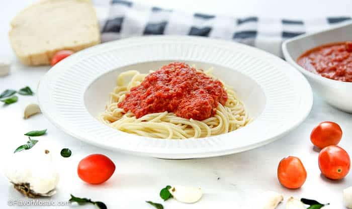 horizontal photo of white bowl with spaghetti with a heaping mound of marinara sauce on top.