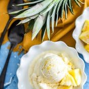 Overhead view of single serving of pineapple ice cream in white bowl with blue background with whole pineapple sliced vertically with orange napkin and 2 spoons.
