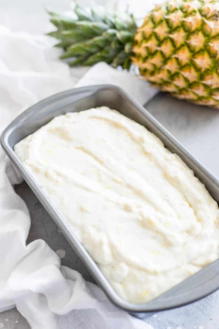 Pineapple Ice Cream in metal loaf pan on gray counter with white napkin and fresh whole pineapple on the side.