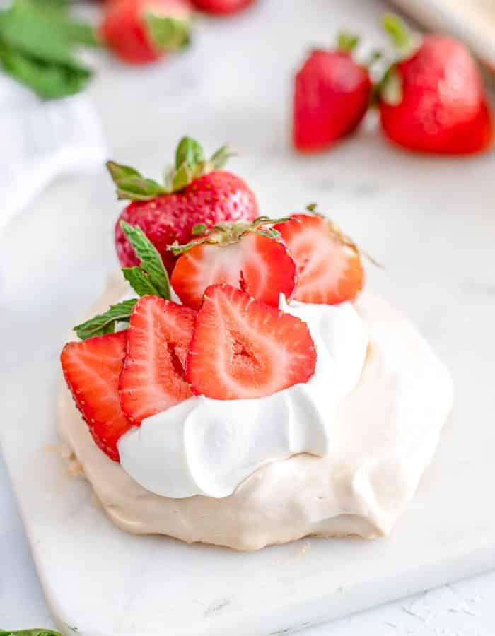 Strawberry Mini Pavlova sitting on white marble with fresh strawberries in the background.