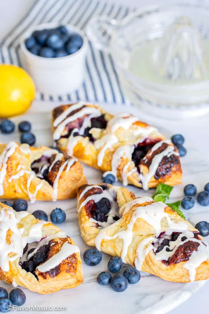 vertical view 4 blueberry puff pastry with cream cheese glaze with lemon and white cup of fresh blueberries sitting on blue and white striped napkin in the background with a cup of water.