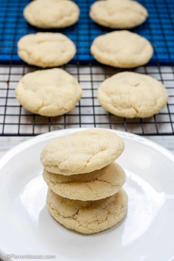 White plate with 3 sugar cookies stacked on top of each other on the plate with 6 cookies on a backing rack in the background with a blue napkin under the top 4 cookies.