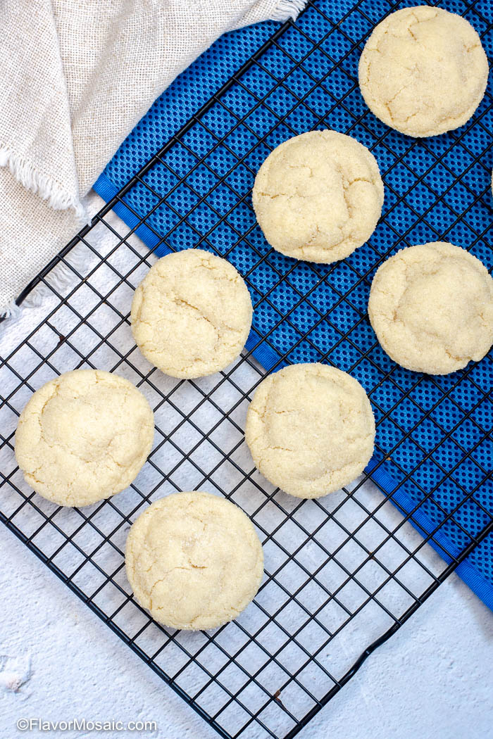 Overhead view of sugar cookies on baking rack with a blue background under half the cookies on the right.