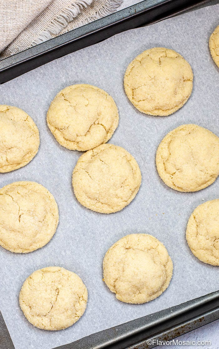 Overhead view of sugar cookies on a parchment covered baking sheet