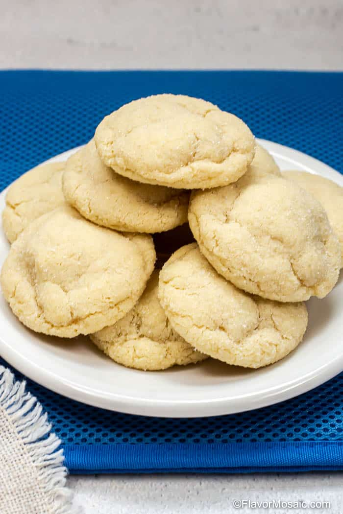 A white plate with lots of thick sugar cookies stacked in a pile on top of the plate.