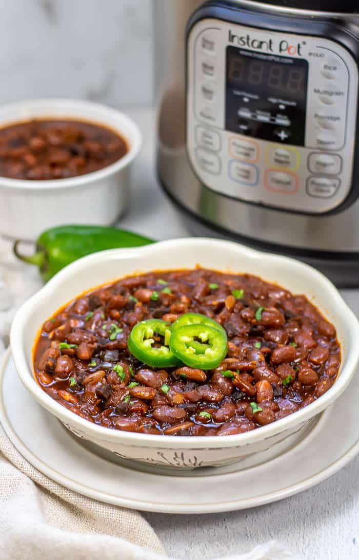 White bowl of Instant Pot Baked Beans sitting on top of white plate in front of Instant Pot with a whole jalapeño and a smaller bowl of baked beans in the back.