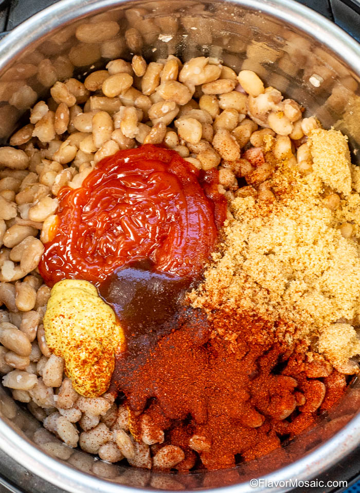 Overhead view of cooked beans with ketchup mustard, molasses, brown sugar, seasonings before it is pressure cooked a second time.