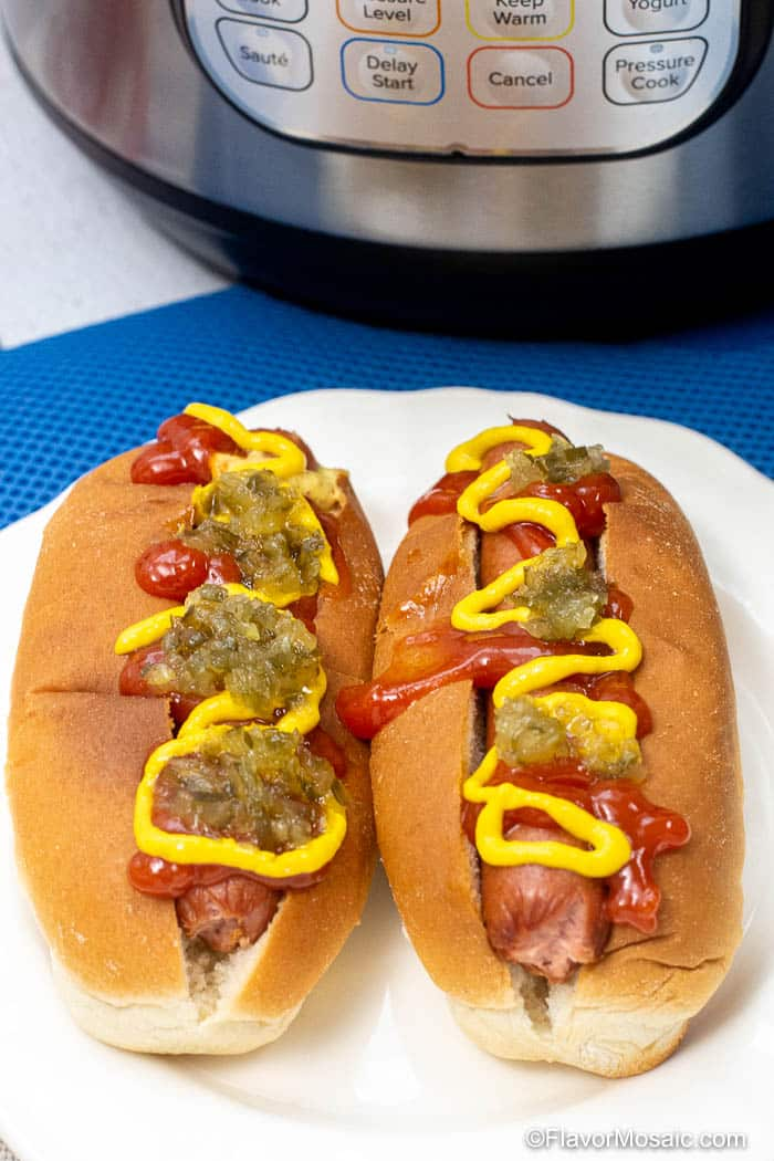 2 dressed hot dogs in front of Instant Pot.