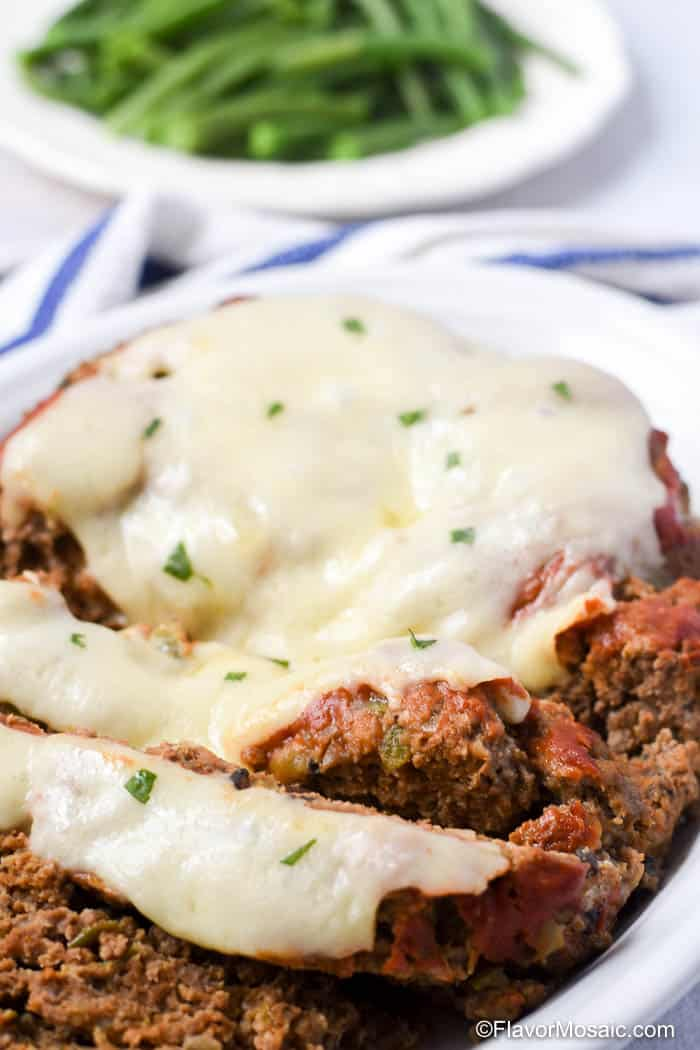 Whole meatloaf partially sliced showing melted cheese on top with plate of green beans in the background.