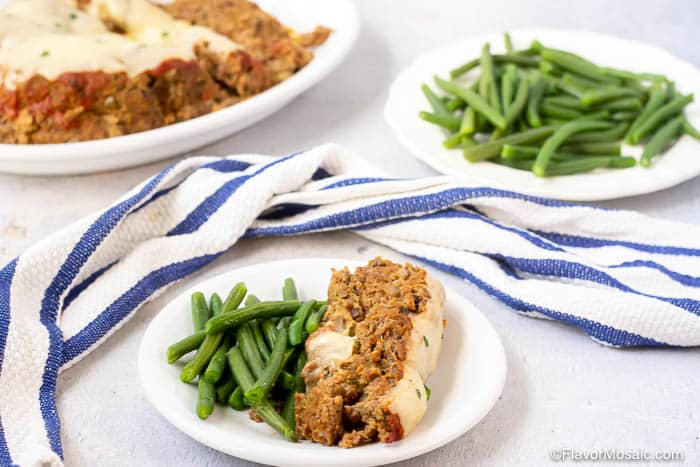 Single serving Instant Pot Meatloaf on white plate with green beans with platter of meatloaf and plate of green beans in the background with a white and blue striped napkin.