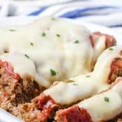 White Platter of cheese covered Instant Pot Philly cheesesteak Meatloaf with a plate of green beans in the background.