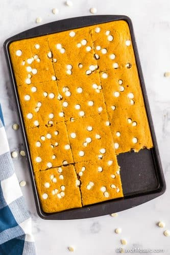 Overhead view Pumpkin Sheet Pan Pancakes in baking pan with blue and white checkered napkin on the left side and white chocolate chips scattered around it on a marble counter.