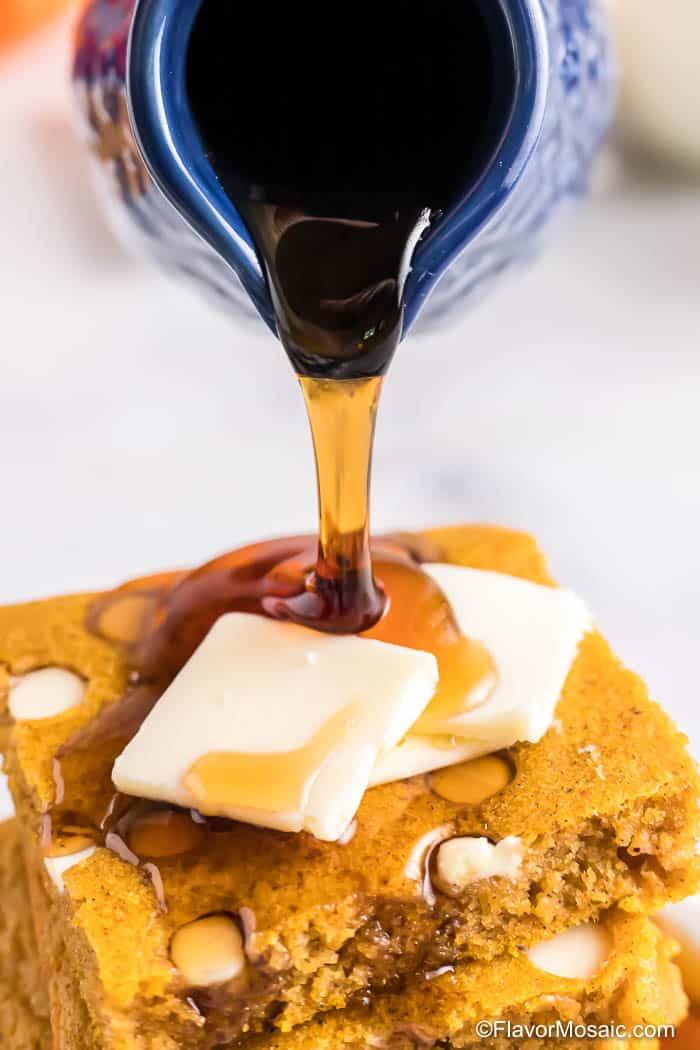 Close up side view of syrup being poured from a blue pitcher over the top of a stack of squares of Pumpkin Sheet Pan Pancakes with 2 pats of butter on top.