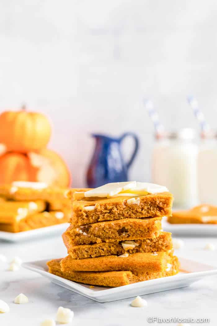 Side view of stack of 4 square-cut Pumpkin Sheet Pan Pancakes on white plate sitting on marble counter with more plates of stacked pumpkin sheet pan pancakes with a stack of real pumpkins on the left, a blue pitcher, and 2 glasses of milk with straws in the background.
