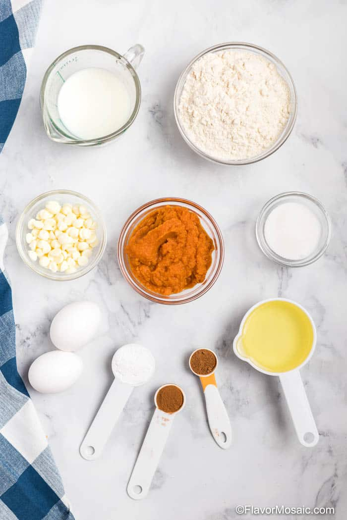 Overhead view of individual bowls of ingredients for Pumpkin Sheet Pan Pancakes on a marble counter with the edge of a blue checked napkin on left