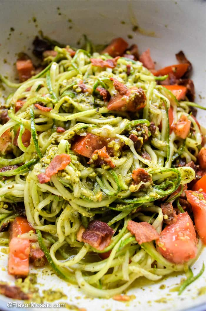 Close up of Zucchini Noodles with Pesto and Bacon in a bowl.