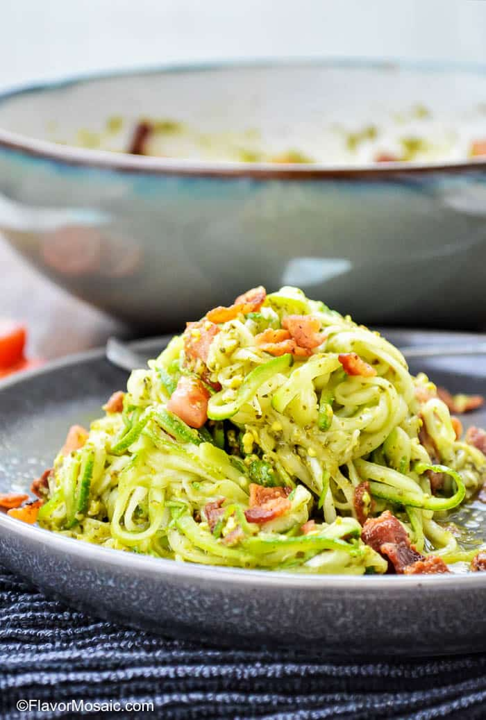 Plate with a heaping pile of zucchini noodles with pesto and bacon with a large bowl in the background.
