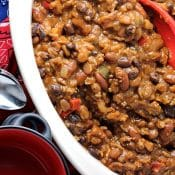 Overhead view of slow cooker with Cowboy Baked beans with bandanas and spoons on the side.