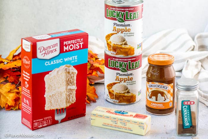 Ingredients in packages sitting on counter, including red box white cake mix, 2 cans apple pie filling, a jar caramel sauce, jar of cinnamon, and one stick of butter.