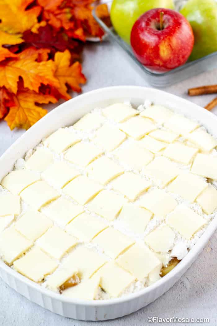 Photo of pats of butter covering the Apple Dump Cake in a white baking dish before it goes in the oven.