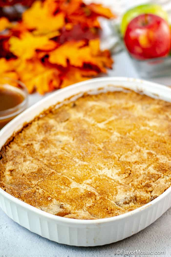 Whole Apple Dump Cake in white baking dish after baking. with fall leaves and glass bowl of red and green apples in the background.;