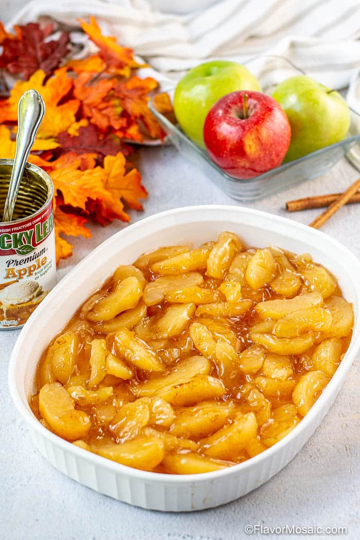 White baking dish filled with 2 cans of apple pie filling that has been combined with cinnamon. In the background are a partial view of an empty can of apple pie filling with a spoon in it, fall colored leaves, and red and green apples.
