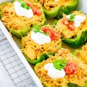 White Baking dish on wire rack with marble background filled with 5 Chicken Fajita stuffed peppers.