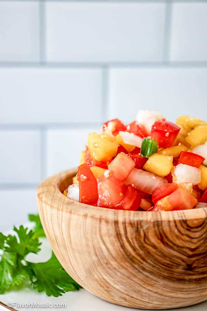 wood bowl of fresh peach salsa.