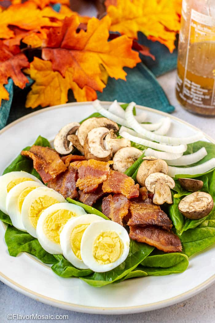 Spinach Salad with sliced hard boiled eggs, chopped bacon, sliced mushrooms, and sliced onions with a bottle of warm bacon dressing and fall leaves in the background.