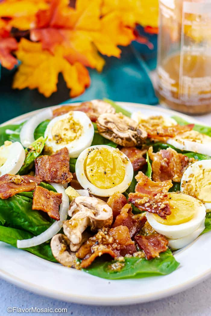 Spinach Salad with Warm Bacon Dressing on white plate with hard boiled eggs, bacon, sliced onions, and sliced mushrooms, with fall colored leaves on blue fabric and a bottle of bacon dressing in the background.
