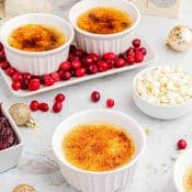 3 white ramekins with creme brûlée surrounded by cranberries and white chocolate chip and gold Christmas decorations.