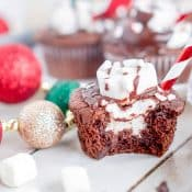 Hot Chocolate Cupcake showing marshmallow filling inside and marshmallow and chocolate ganache on top with candy cane straw, surrounded by chocolate chips, mini marshmallows and Christmas ornaments.