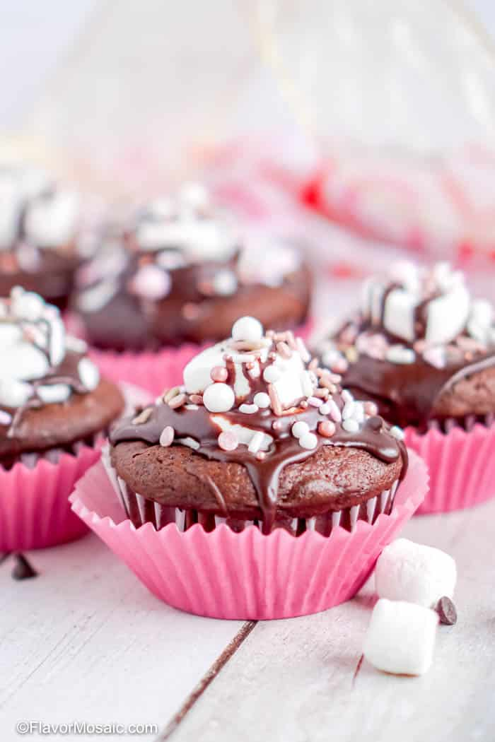 Photo of Hot Chocolate Cupcakes topped with crushed candy canes and pink cupcake wrappers.