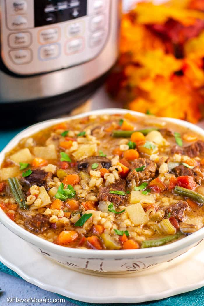 White Soup Bowl on white plate with Instant Pot Beef And Barley Soup with partial view of Instant Pot and fall colored leaves in the background.