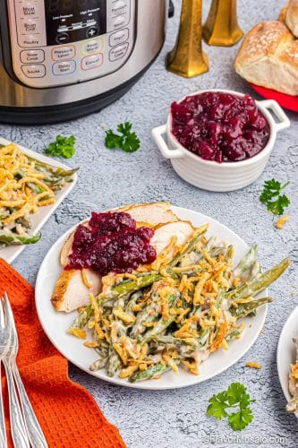 Thanksgiving dinner plate with green bean casserole, sliced roast turkey and cranberry sauce.