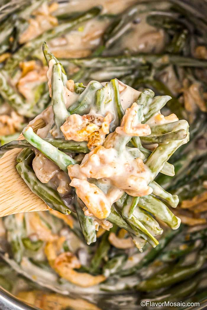 Overhead photo of spoonful of green bean casserole over the green bean casserole in an Instant Pot pressure cooker.