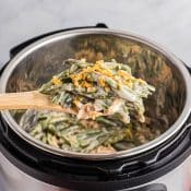 Holding spoonful of green bean casserole over Instant Pot with the rest of the green bean casserole
