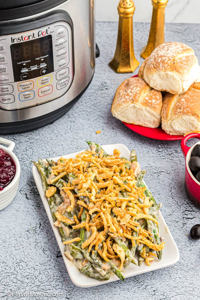 Platter of Green bean Casserole in front of Instant Pot with rolls and cranberry sauce on the side.