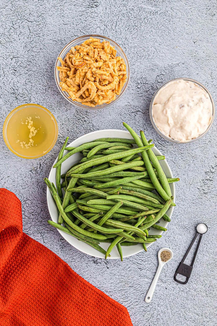 Overhead view ingredients for Instant Pot Green Bean Casserole including green beans broth cream of mushroom soup, and french fried onions.
