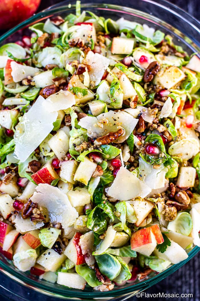Overhead view showing tossed Shaved Brussels Sprouts Salad with chopped apples, pomegranate seeds, chopped pecans, and shaved parmesan cheese.