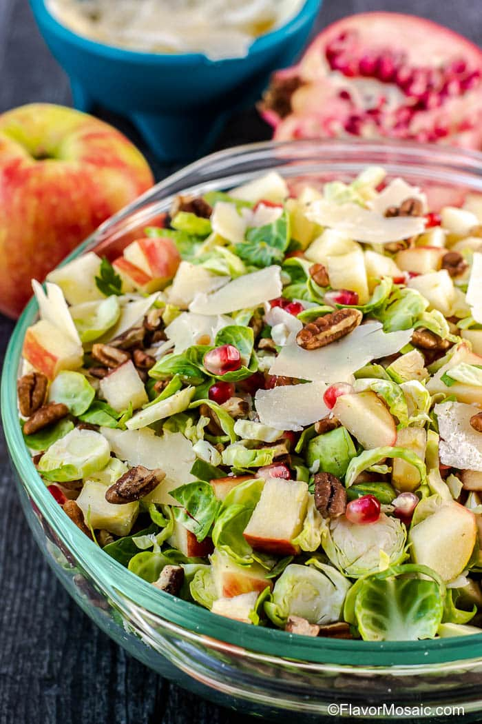 Glass bowl on dark gray background with apple and sliced pomegranate in the background and a tossed Shaved Brussels Sprouts Salad in bowl.