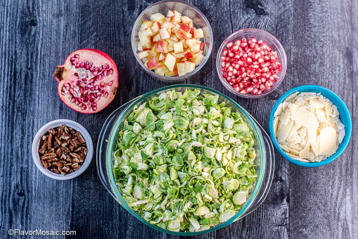 Overhead view of ingredients for Shaved Brussels Sprouts Salad including shredded brussels sprouts, chopped pecans, pomegranate seeds, chopped apples, and shaved parmesan cheese.