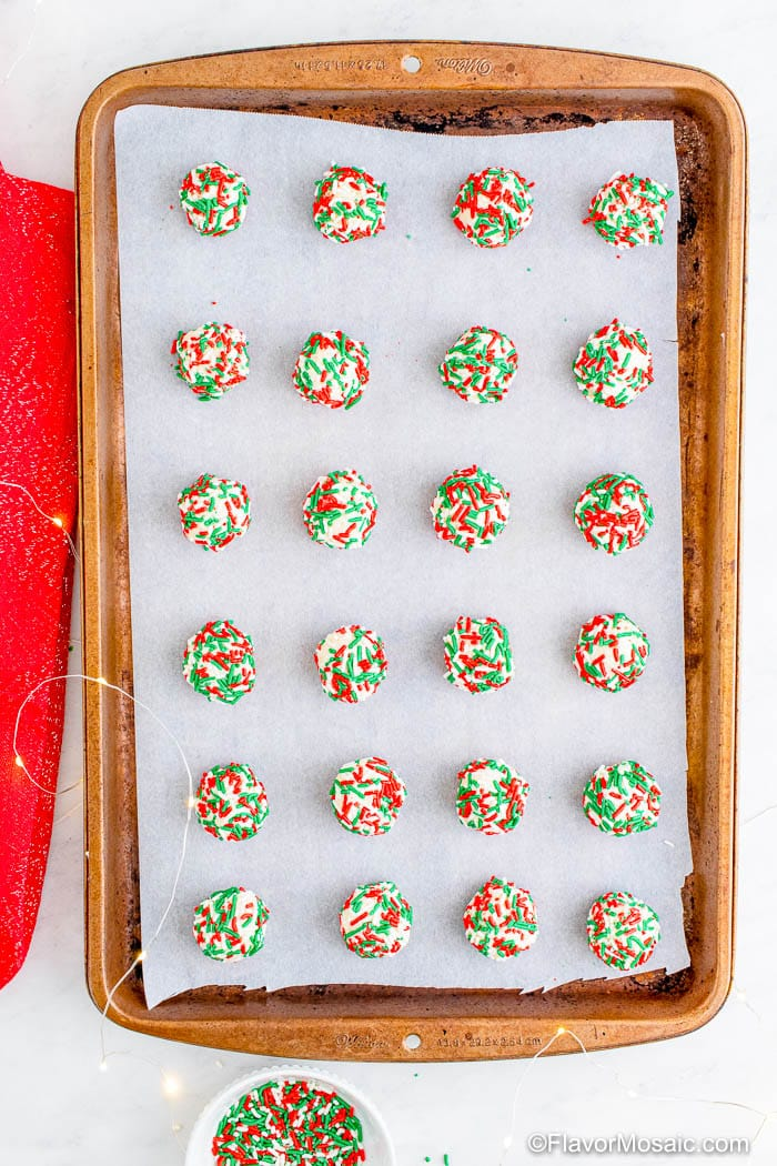 Overhead view of balls of shortbread cookies covered in red and green sprinkles.