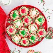 Overhead view of red platter with shortbread thumbprint cookies covered in red and green sprinkles with red green and white buttercream frosting on a marble counter with a red napkin, glass of milk and red and green sprinkles in the background. A few cookies are placed in front of the platter.