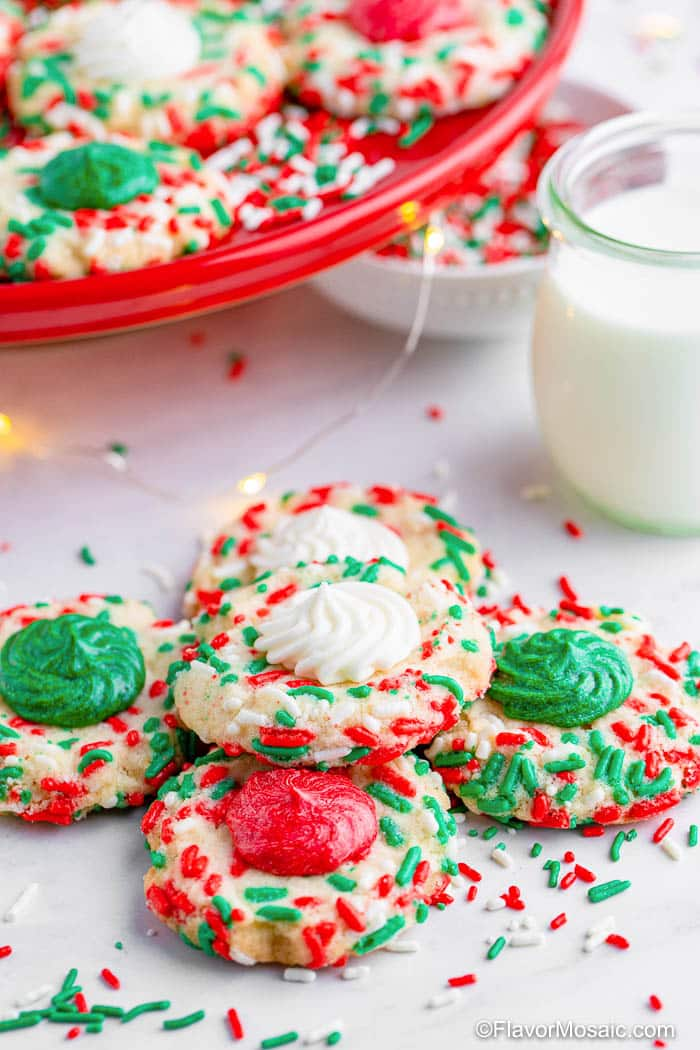 4 Christmas Thumbprint cookies, covered in sprinkles, in front with one thumbprint cookie stacked on the others in front of a glass of milk and partial view of a red cookie platter with more Christmas Thumbprint cookies.
