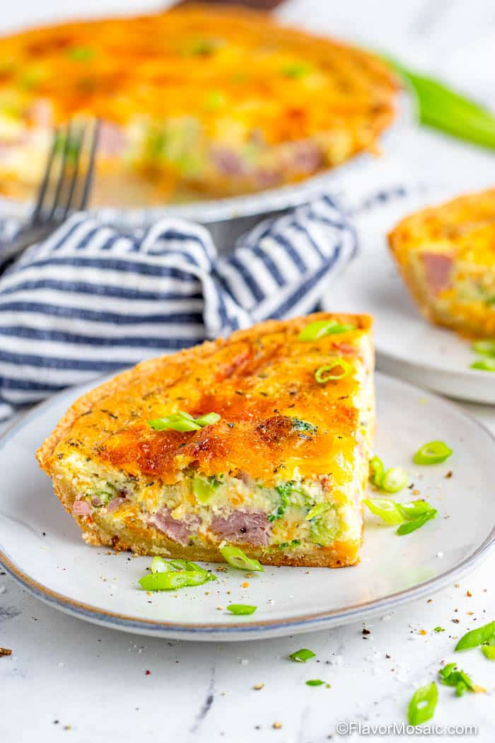 View on a single slice of ham and broccoli quiche on a white plate with a fork and blue and white striped napkin, as well as a whole quiche and partial view of the corner of another slice of quiche in the background.