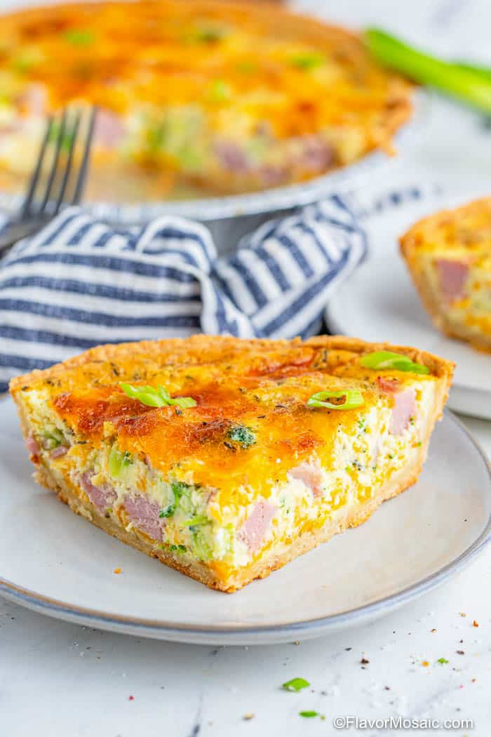 A white plate with a large slice of Ham and Broccoli Quiche with a blue and white napkin with the rest of the quiche pie in the background. Partial view of green onions on the top left.